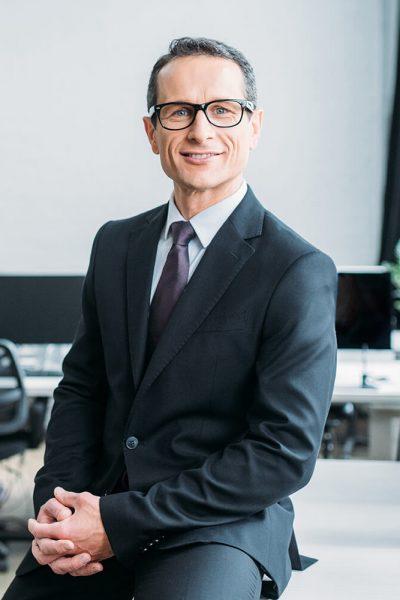 smiling-businessman-in-eyeglasses-sitting-on-table-V5AWVKC.jpg